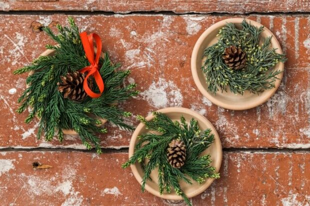 Christmas wreaths made from pine twigs on wooden table