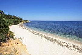 das Bild zeigt einen Strand am Mittelmeer mit blauem Himmel