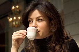 das Bild zeigt eine Frau, die Espresso trinkt