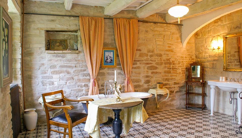 das Bild zeigt ein mediterranes badezimmer in Italien mit freistehender gusseiserner wanne
