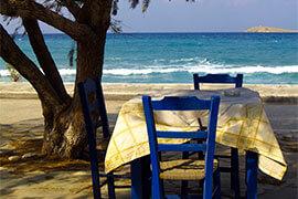 Das Bild zeigt einen Tisch mit 2 blauen Stühlen am Meer