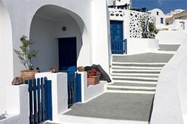 das Bild zeigt ein blau weißes Haus in einem griechischen Dorf