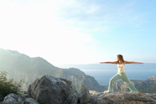 das Bild zeigt eine Frau am Meer, die Yoga übt