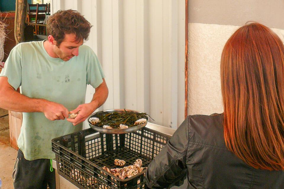 das Bild zeigt einen Austerfarmer, der Austern für Gäste öffnet
