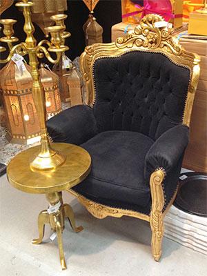 das Bild zeigt einen schwarzen Boudoir-Sessel mit goldenen Füßen und Lehene