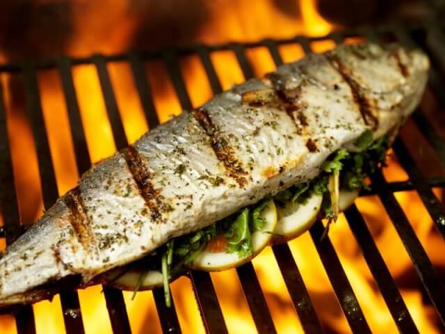 das Bild zeigt einen gebratenen Fisch auf dem Grill