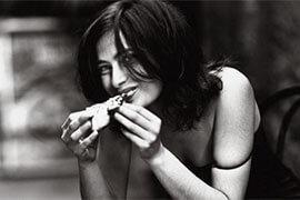 das Bild in schwarz-weiss zeigt eine lächelnde Frau, die Pizza mit der Hand isst
