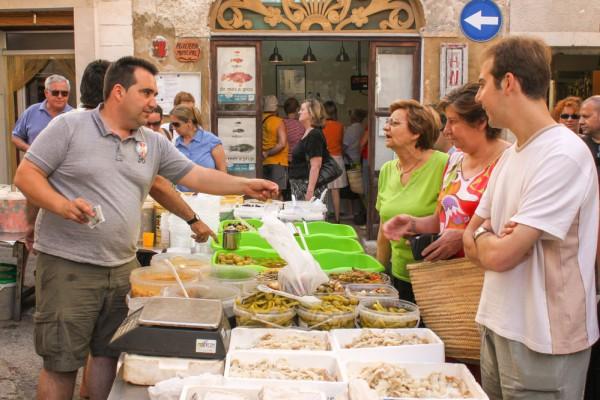 das Bild zeigt einen Fischverkäufer und einige Kunden beim Handeln
