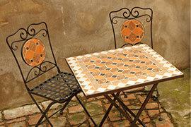 Das Bild zeigt einen mediterranen Mosaiktisch und 2 Metallstühle