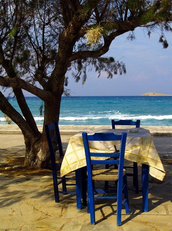 Das Bild zeigt einen Tisch mit 2 blauen Stühlen am Meer an einem Baum