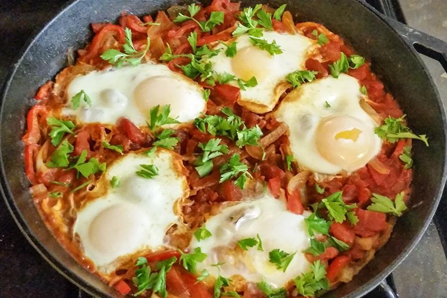 Shakshuka: eine Sauce aus Tomaten, Chili und Zwiebeln mit pochierten Eiern © Wikipedia