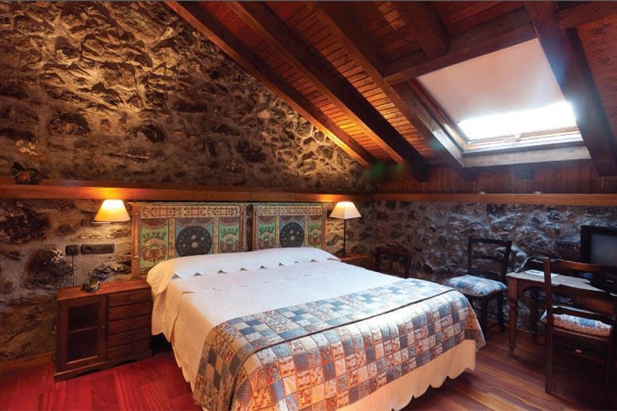 Ein Zimmer unter dem Dach mit wuchtigen Steinblöcken und Holzdecke