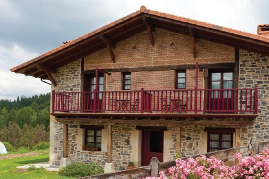Das Hotel Etxegorri von außen mit rotem Balkon