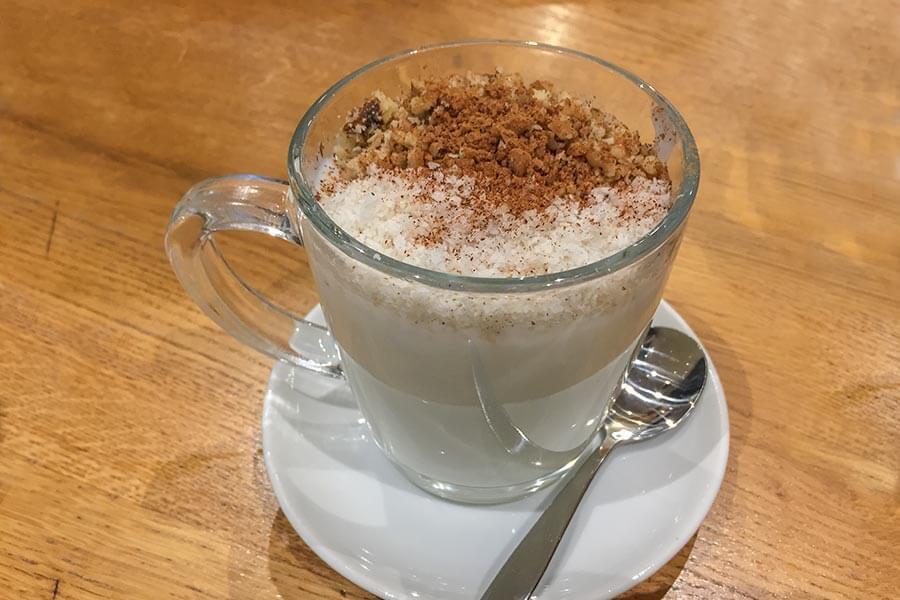 Sahlab in einer Tasse mit Zimt, Nüssen und Kokosraspeln