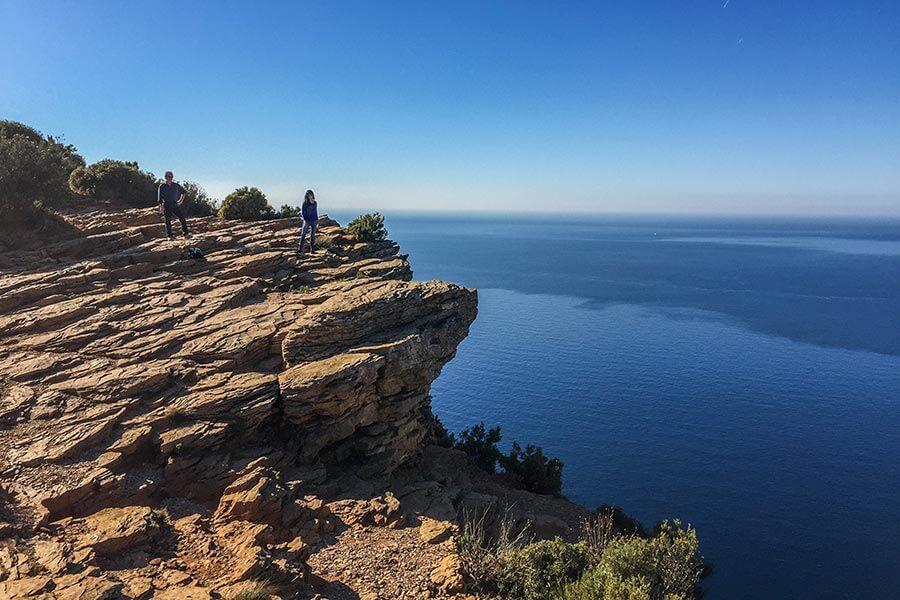Weiter Blick von den Felsen aufs Meer, eine Frau und ein Mann auf den Klippen