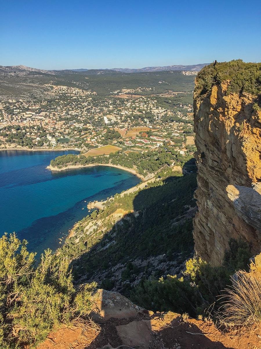 Blick auf Cassis von der Steilküste aus, oben direkt am Abgrund steht eine Frau