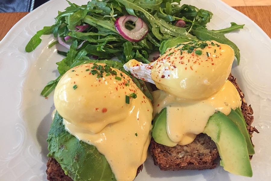 Egg Benedict mit Avocadoscheiben auf Vollkornbrot