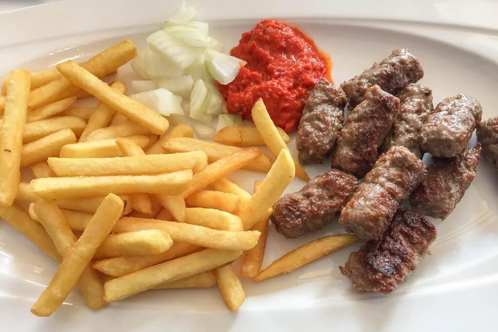 Ćevapčići mit Ajwar, rohen Zwiebeln und ok, Pommes © Siegbert Mattheis