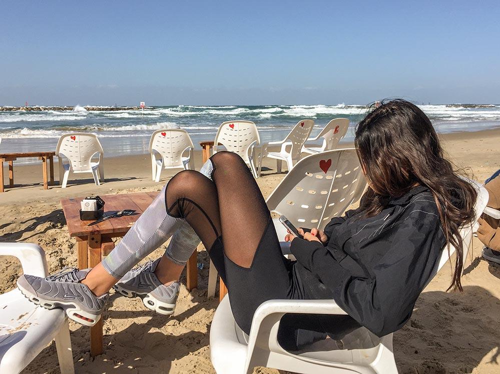 Junge Frau chattet am Strand