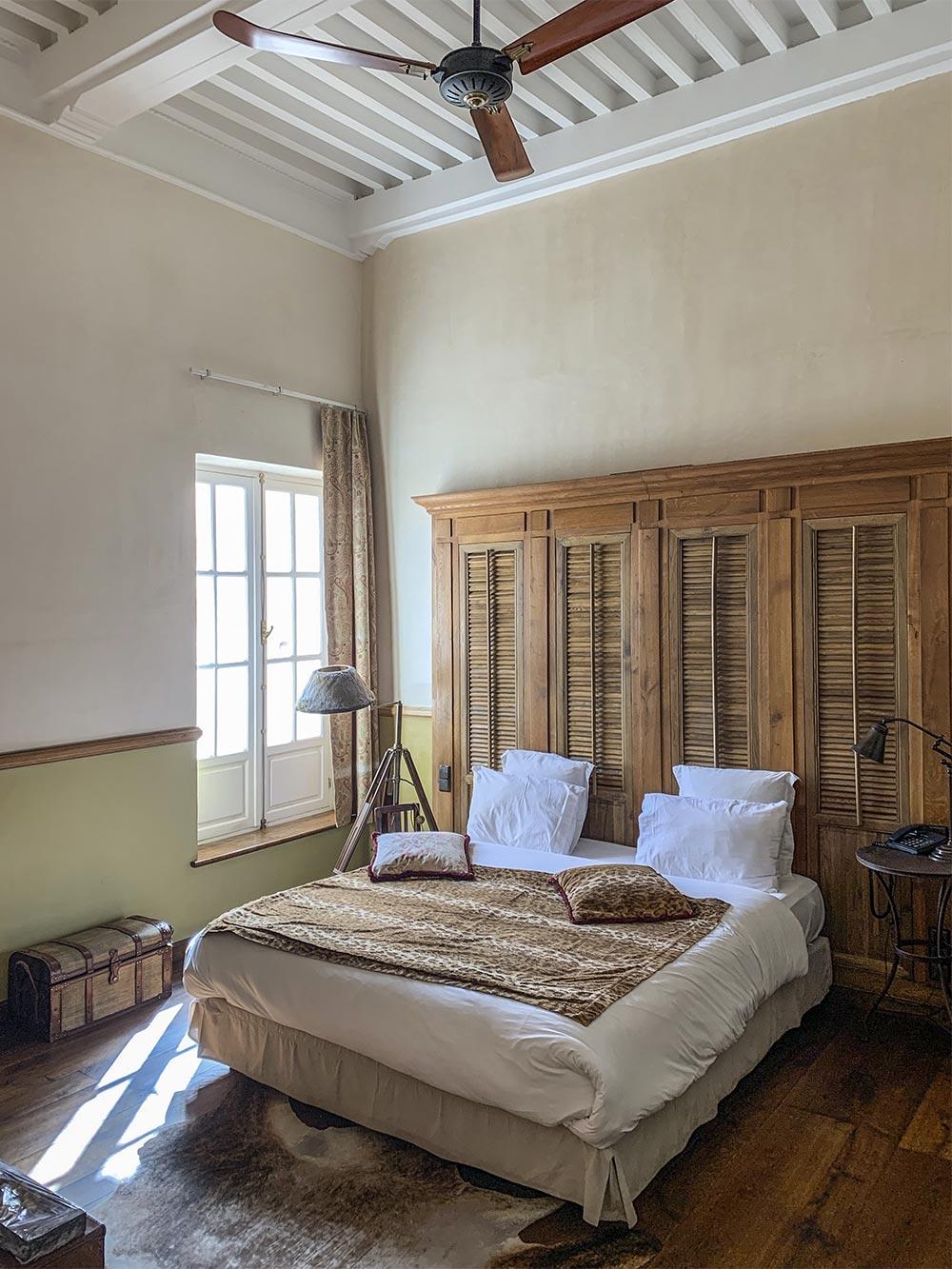Mit Leopardendecke bezogenes Bett vor einem Schrank, links ein helles fenster, oben ein Ventilator