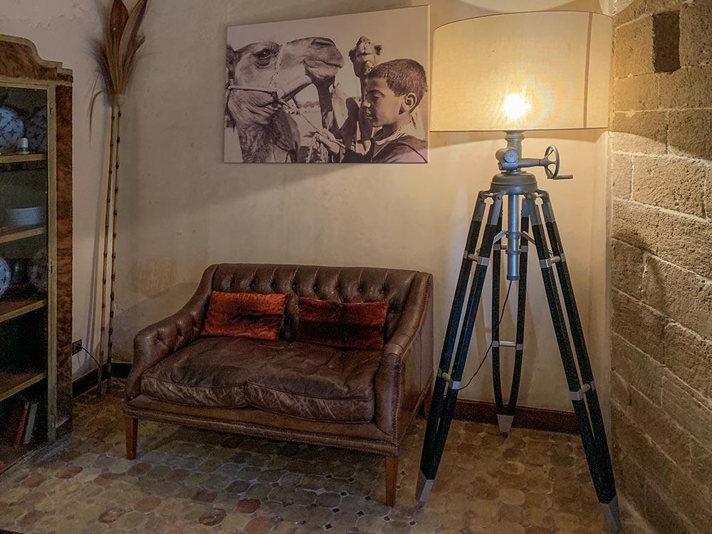 Ledercouch und Lampe auf altem Holzstativ