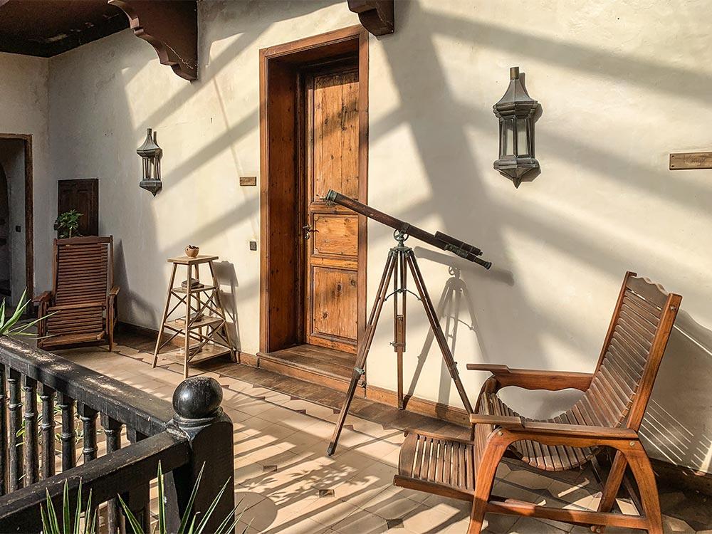 Patio mit altem Fernrohr und Holzstühlen