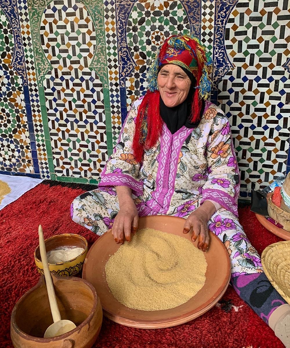 Berberfrau bei der Couscouszubereitung mit etwas Öl