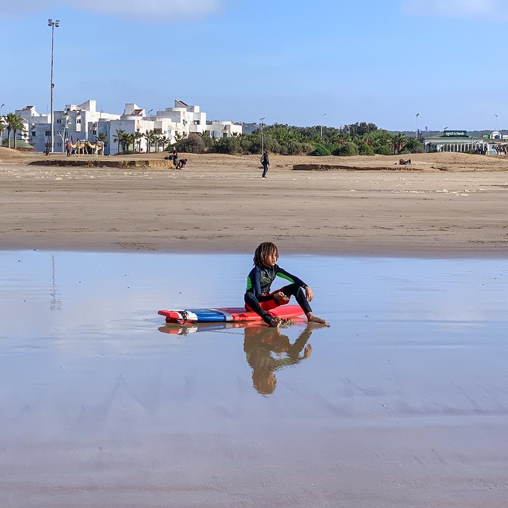 Ein kKind sitzt auf dem Surfboard und wartet auf die richtige Welle
