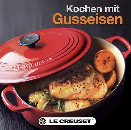 Buchtitel Kochen mit Gusseisen, ein gebratenes Hähnchen in einem roten le Creuset-Bräter