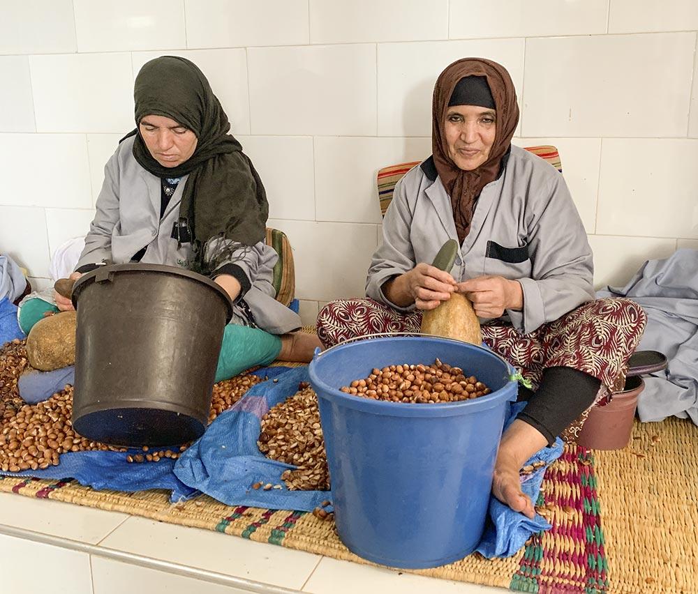In mühevoller Arbeit schlagen die Berberfrauen die Samenkerne aus den Nüssen