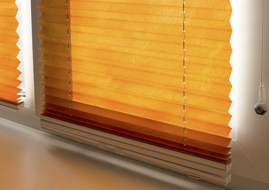 Ein Plissee-Sonnenschutz bringt Sichtschutz und wie hier einen wunderbar warmen Farbton in den Innenraum