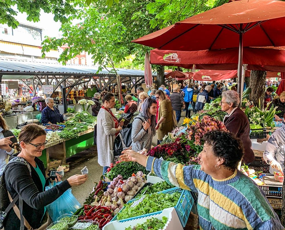Der große Markt in Pula neben der Markthalle, einem ehemaligen Bahnhof, Marktfrau und Kundin im lebhaften Gespräch