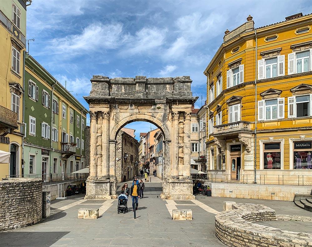 Der antike Sergierbogen, rechts und links bunte Häuser