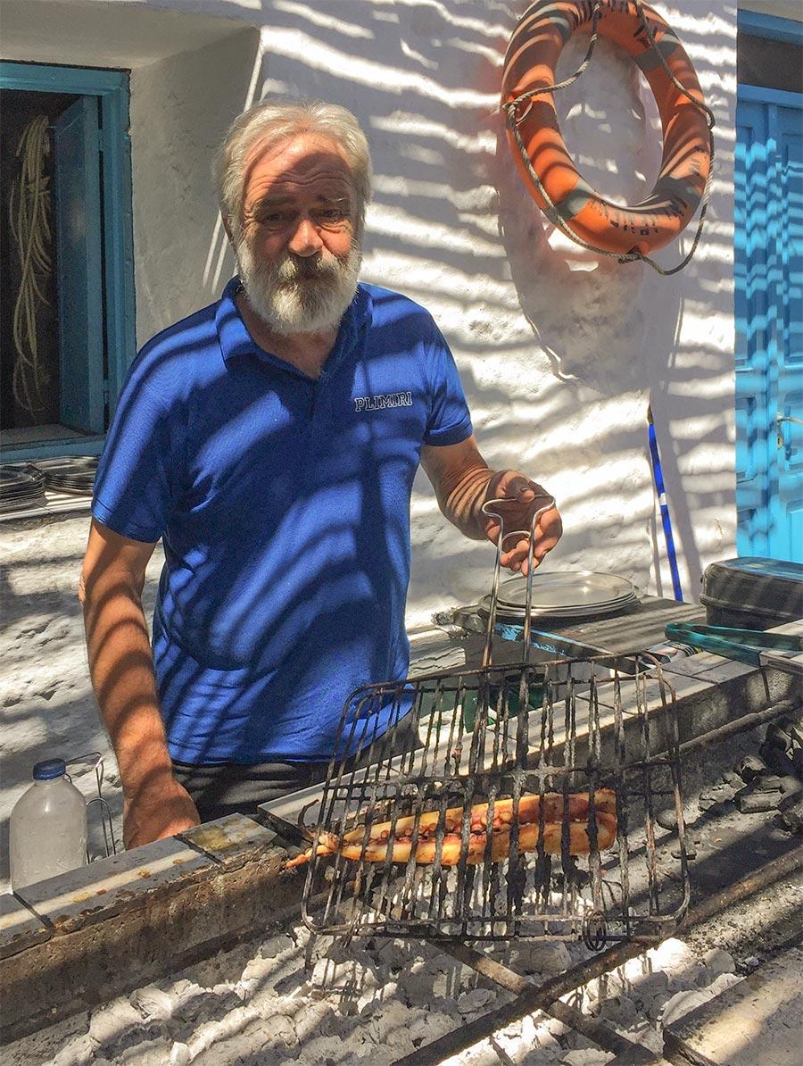 Ein älterer Mann mit Bart und Oktopus auf dem Grill in Griechenland