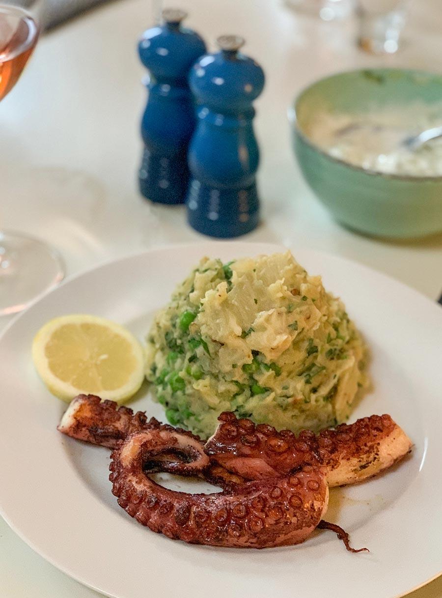 Köstlicher gebratener Oktopus, hier als Hauptmahlzeit mit Kartoffel-Erbsen-Zitronenstampf
