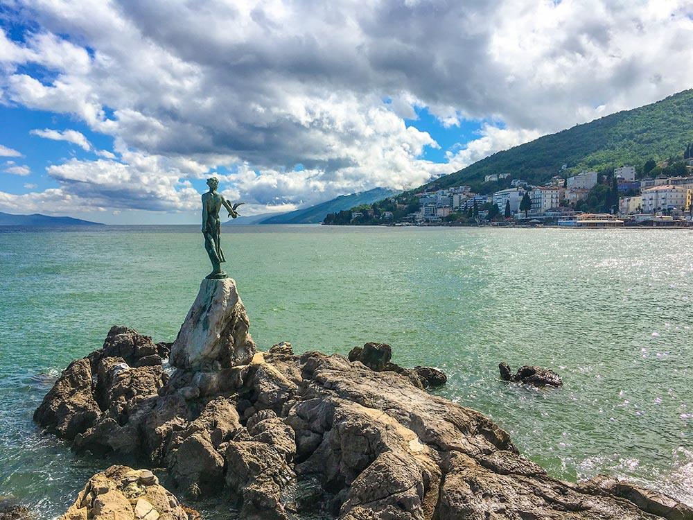 Staue Mädchen mit der Möwe auf Felsen am Meer
