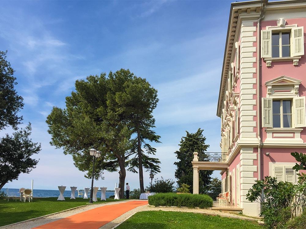 Die rosafarbene Villa Poselini, roter Teppich, direkt am Meer
