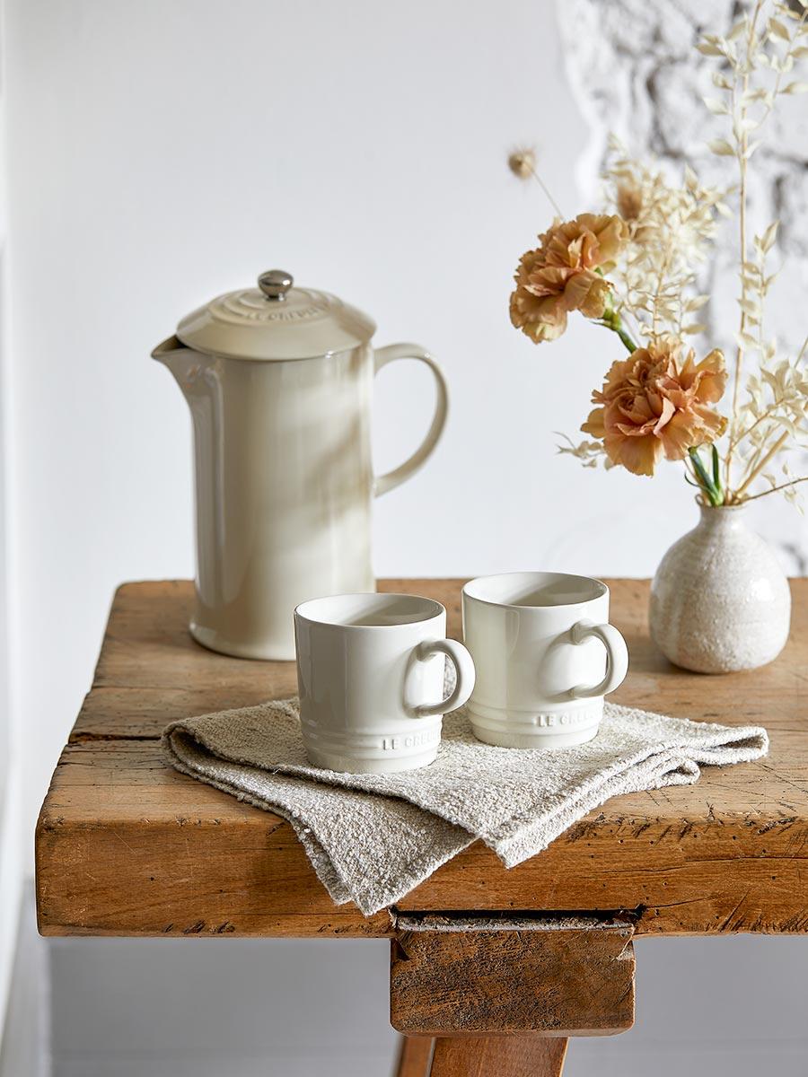 Kanne und 2 Tassen der Meringue-Kollektion auf einem Holztisch