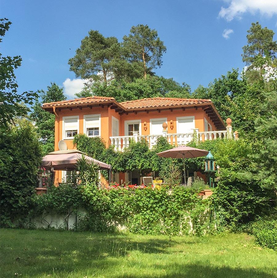 Ockerfarbenes mediterranes Haus im Toskana-Stil inmtten von Grün