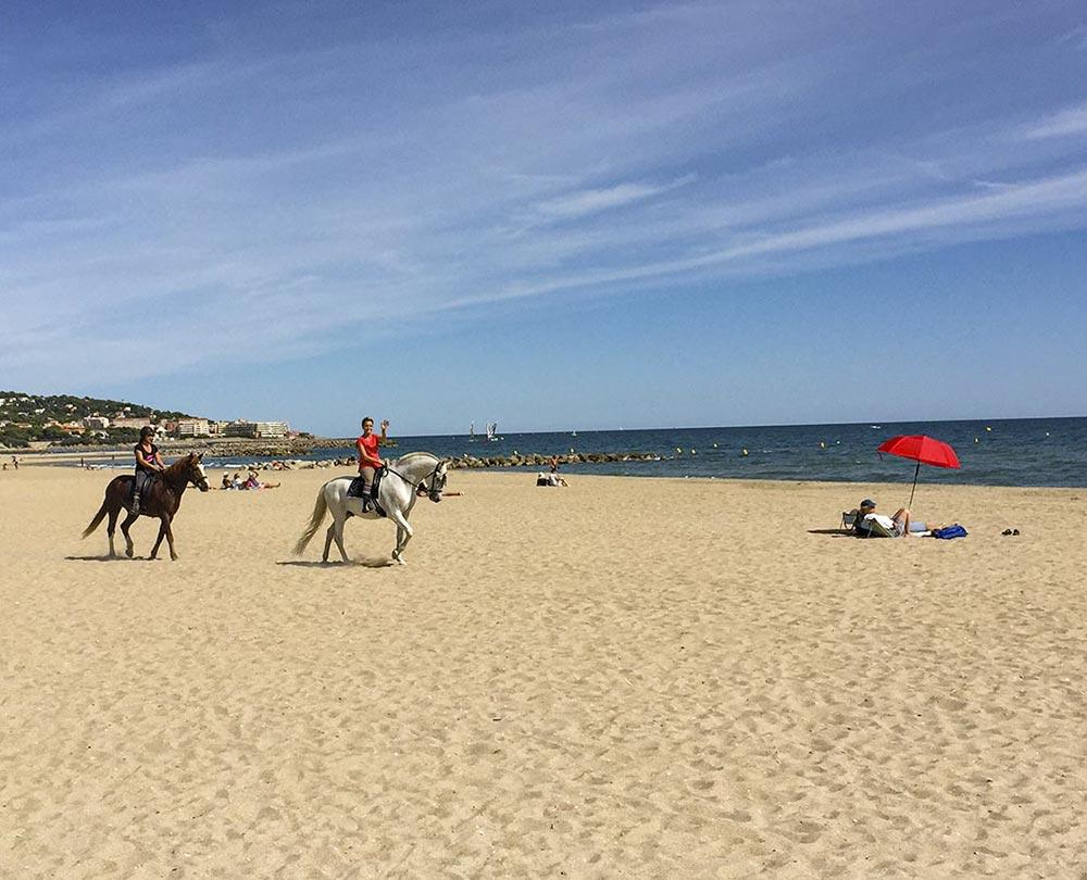 2 Reiterinnen am Strand winken uns