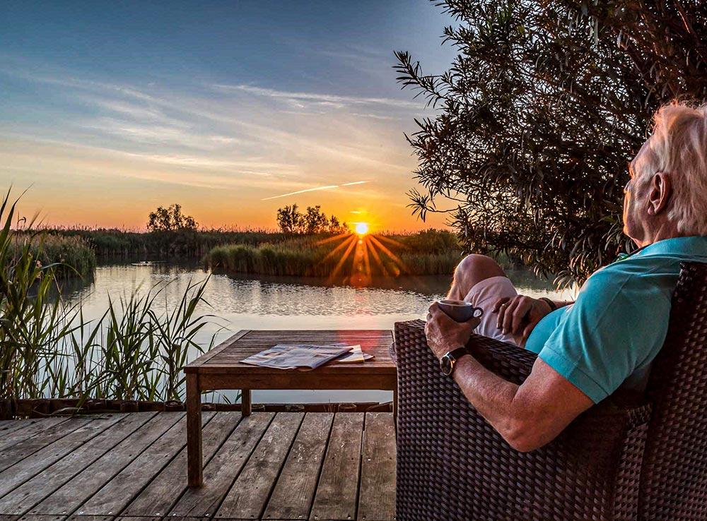 Ein Mann sitzt auf der Terrasse mit Blick in den Sonnenuntergang über der Camargue