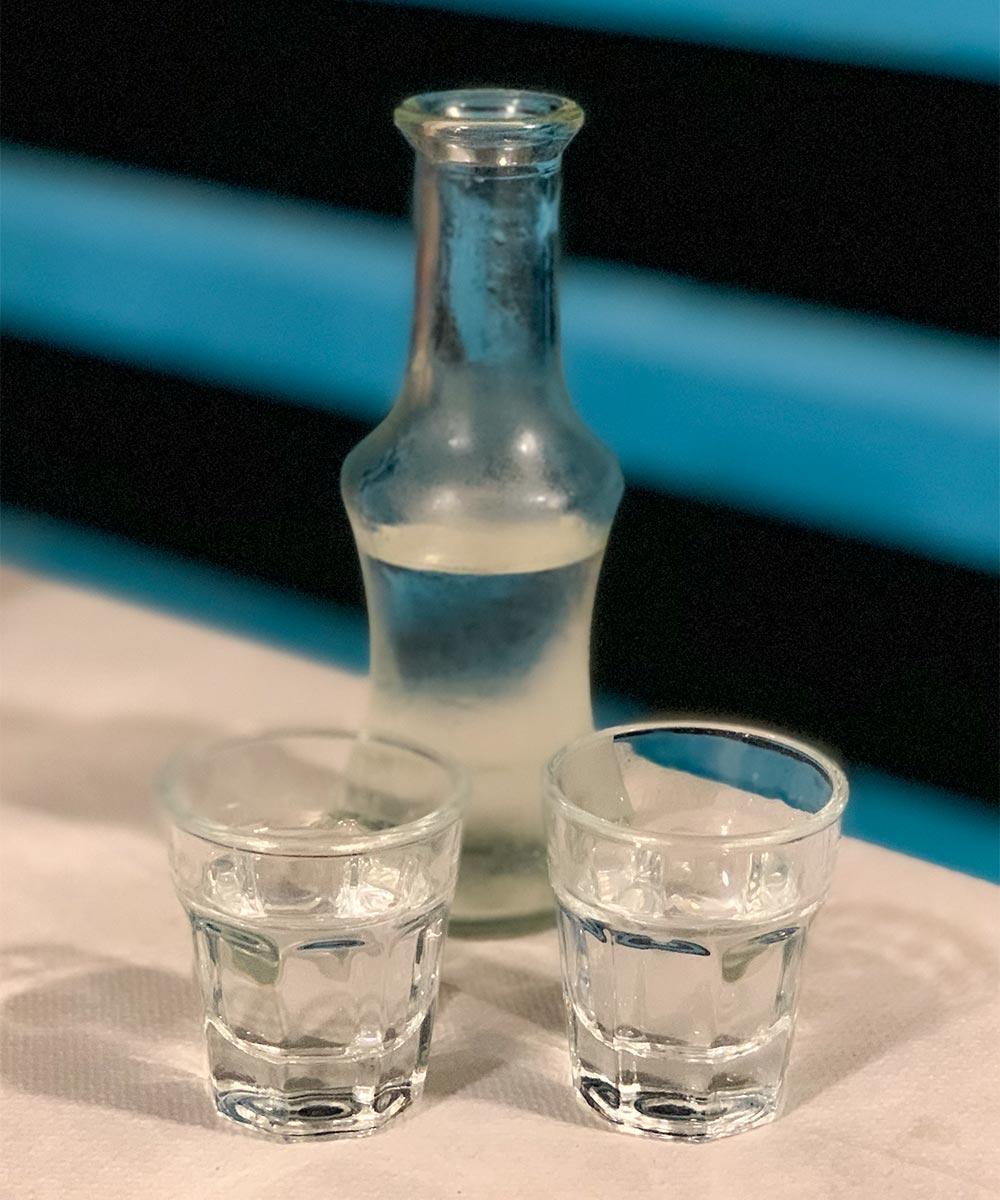 Raki in kleiner Flasche, davor zwei Gläser