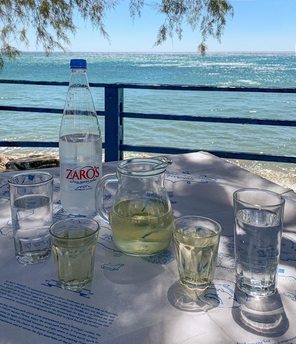 Wasser aus Zaros, Weißwein, auf einem Tisch am sonnigen Meer