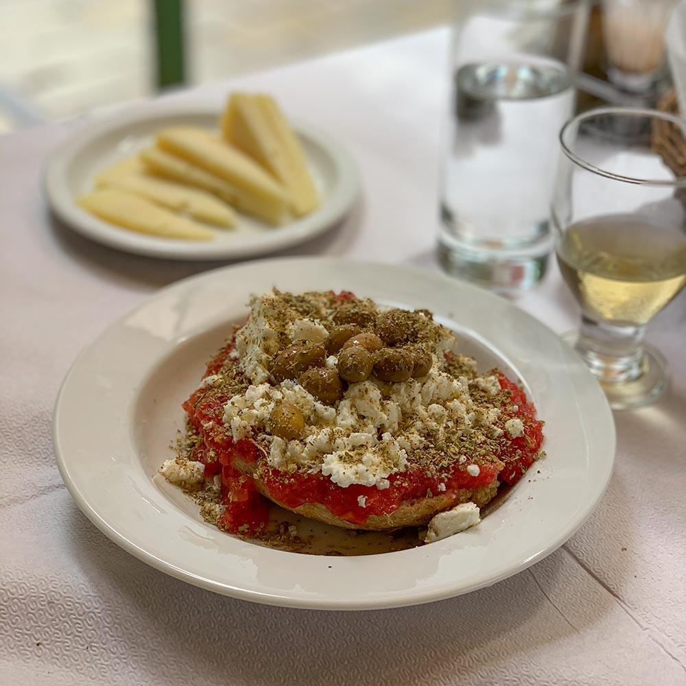 Das klassiche Dakos mit Tomaten und braunen Oliven