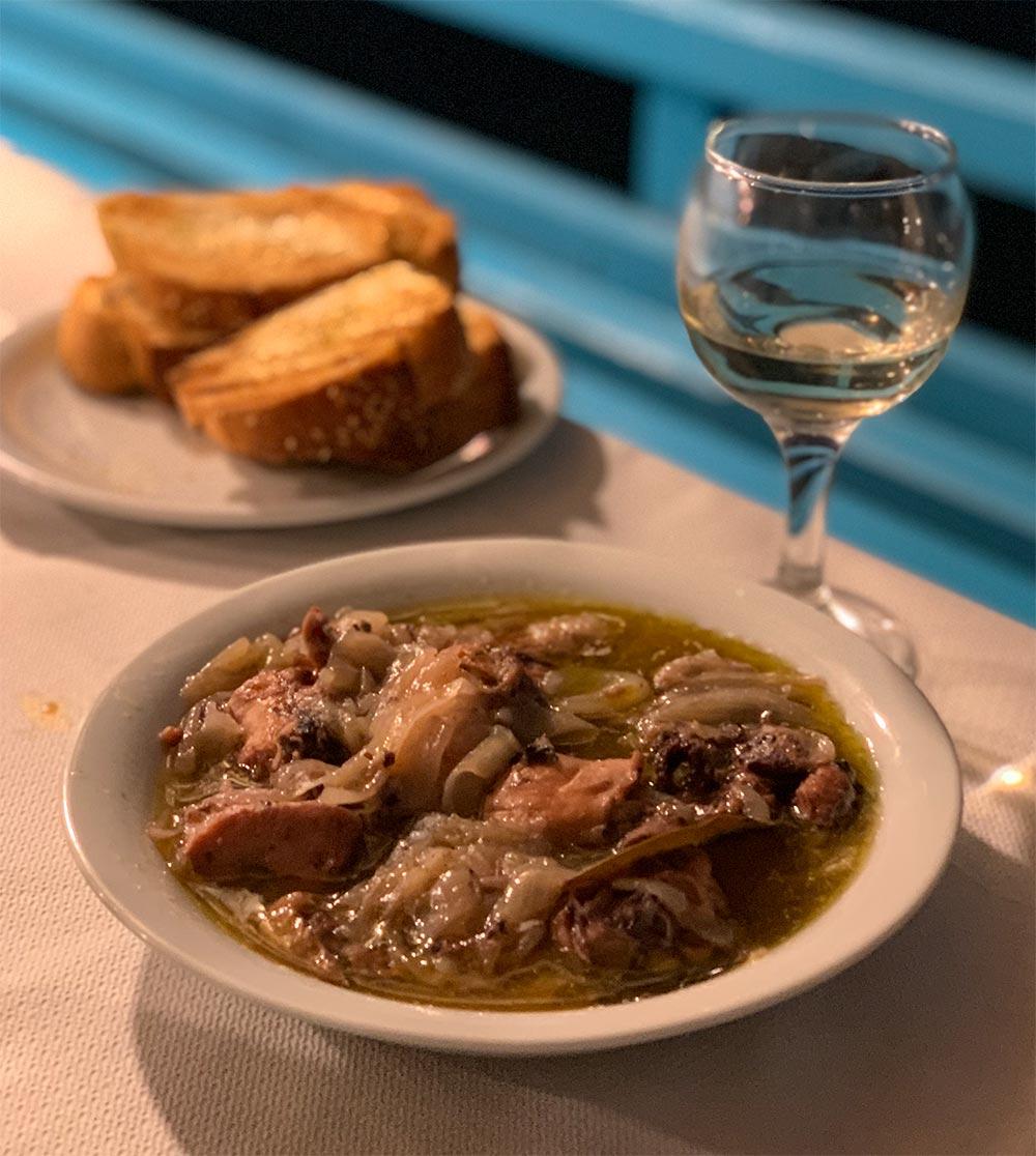 Oktopus in Rotweinsauce mit Zwiebeln, geröstetes Brot und Wein dazu