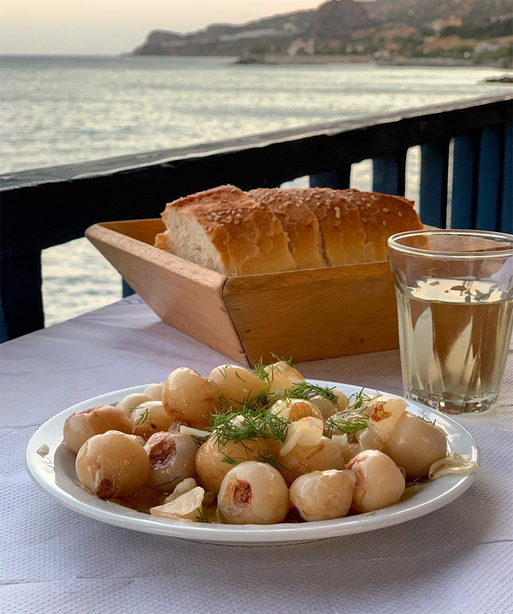 Eingelegte saure Zwiebeln, dahinter Brot, Wein und die Küste