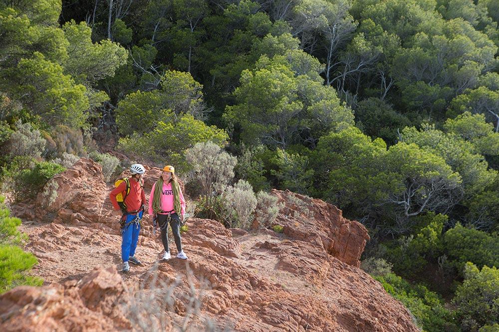 2 Wanderer auf roten Felsen, im Hintergrund Kiefernwald