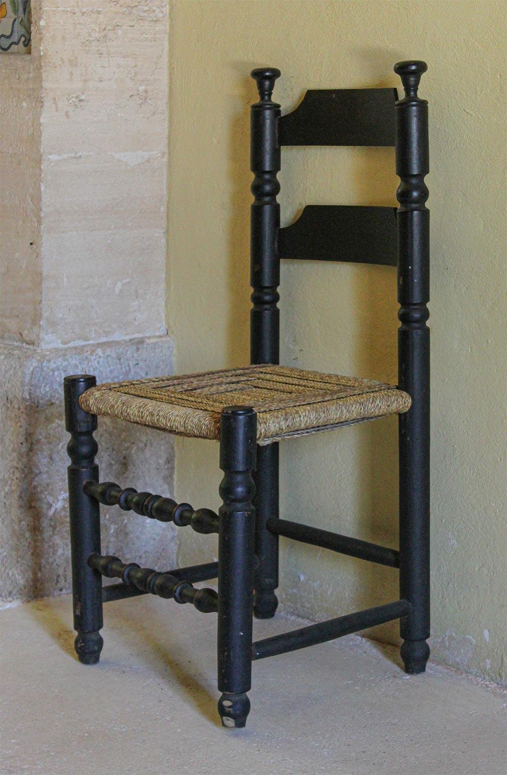 Stuhl aus schwarzem Holz mit Flechtwerk